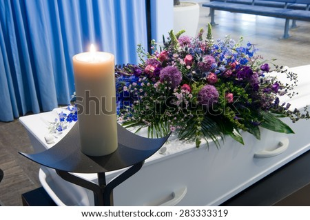 A coffin with a flower arrangement in a morgue and a burning candle - stock photo