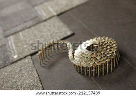 A coil of roofing nails on a new roof in progress - stock photo