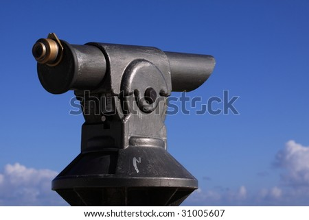 a coin operated antique telescope on a blue sky background