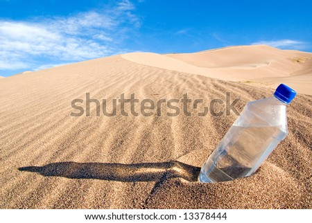 A cold bottle of water sitting in a sand dune - stock photo