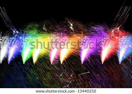 A collage of fireworks giving off a shower of colored sparks.