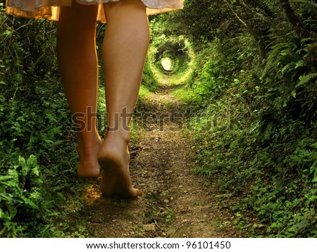 A collage of two images showing giant female legs walking onto a tunnel-like forest path with light at the end - stock photo