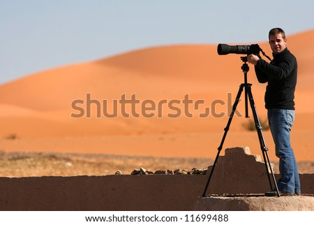 A colleague photographer photographing certain aspects of the desert - stock photo