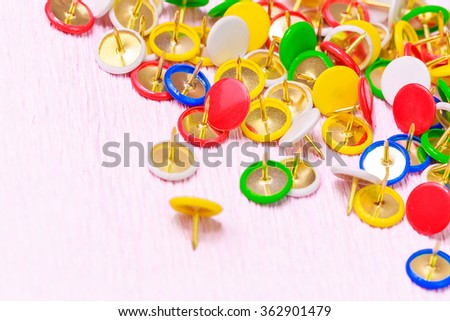 A collection of colorful thumbtacks on the background, space for text - stock photo