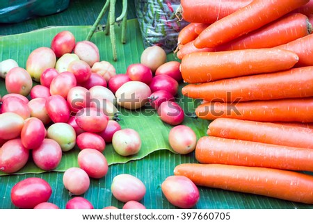 A collection of grape tomatoes and a pile of bright-colored carrots on green banana leaves on a stall at a grocery shop in Thailand - stock photo