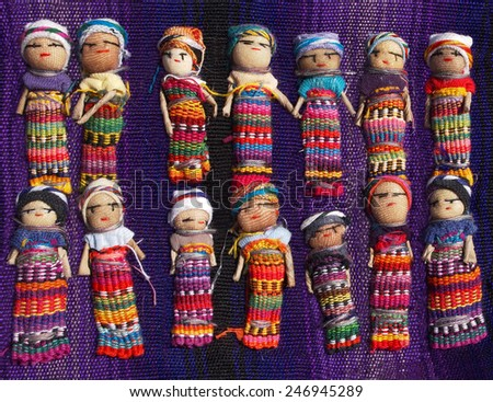 A collection of large, colorful Guatemalan Worry Dolls lined up in two rows on a purple woven blanket. - stock photo
