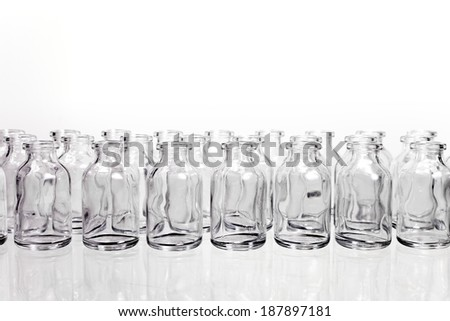 A collection of many small empty scientific vials in rows against a white background. - stock photo