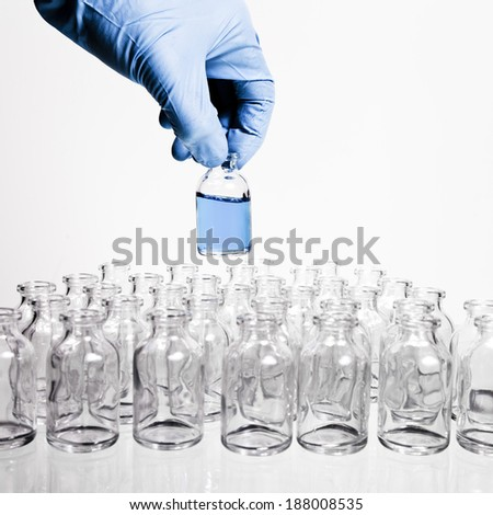 A collection of many small empty scientific vials in rows with a hand wearing a blue latex glove holds one container up. - stock photo