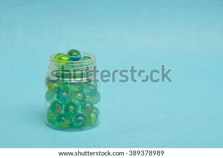 A collection of marbles in a plastic jar displayed on a blue background - stock photo