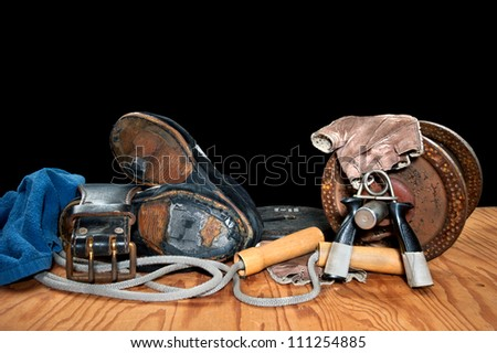 A collection of old exercise equipment including hand grips, dumbell, jump rope and old, torn weightlifting shoes. - stock photo