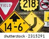 A collection of old road signs on a fence. - stock photo