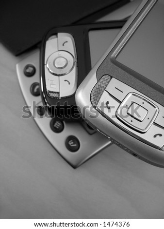 A collection of PDAs ranging from old to the newest in technology. This is a black and white image. - stock photo