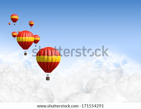 A collection of red and yellow hot air balloon floating above the clouds on a clear blue sky background - stock photo