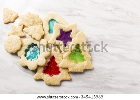 A collection of stained glass Christmas cookies on marble