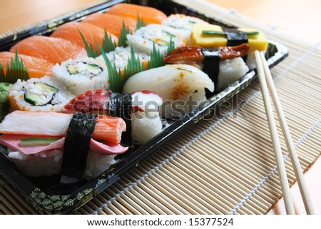 A collection of sushi on a bamboo mat. - stock photo