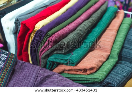 A collection of Thai silk cloths and Multicolored striped,Pile of colorful clothes - stock photo