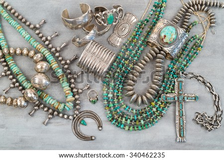 A collection of Vintage Native American Jewelry made of Turquoise and Sterling Silver. Necklaces, cuff bracelets, Squash Blossom and a Silver Cross. - stock photo