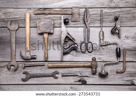 A collection of vintage tools displayed on a wooden bench. - stock photo
