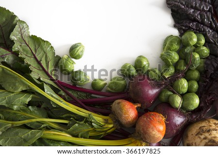 A collection of winter vegetables including beets, brussels sprouts, chard and rutabaga, with copy space