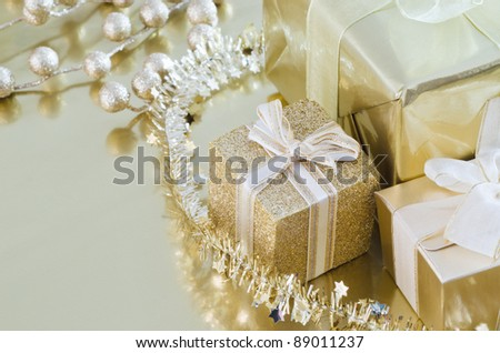 A collection of wrapped and tied Christmas gifts and decorations in gold shiny paper on reflective surface. - stock photo