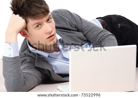 A college guy with a laptop lying on the floor - stock photo