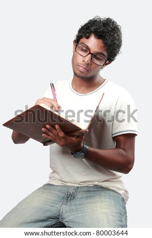 A college student seriously writes on his note book - stock photo