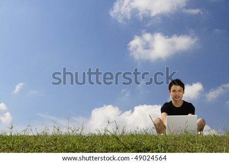 A college student working with his laptop outdoors - stock photo
