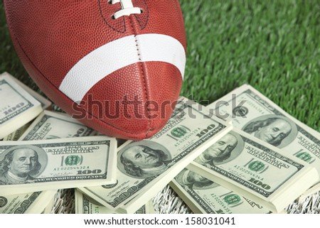 A college style football sits with a pile of money on a green field - stock photo