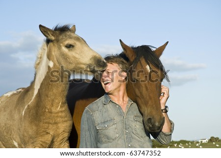 A color photo of a happy laughing forties man having fun and petting his two horses. - stock photo