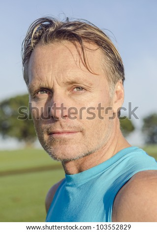 A color portrait of a handsome mature man in his forties with stubble looking into the camera with strength and determination. - stock photo
