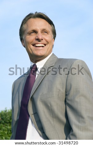 A color portrait of a handsome smiling businessman in his forties. - stock photo