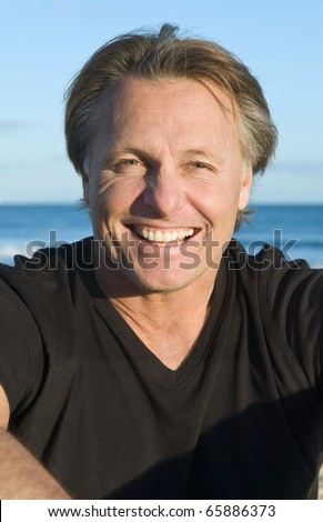 A color portrait of a happy laughing man in his forties. - stock photo