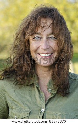 A color portrait of a happy smiling woman in her forties with brown hair and green eyes. - stock photo