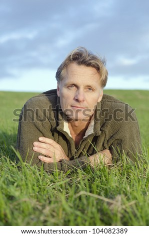 A color portrait of a mature blond haired man laying on the grass and looking at the camera. - stock photo