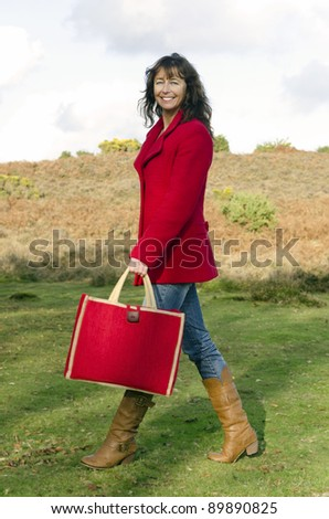 A color portrait of a mature woman in her forties wearing a red coat and holding a red bag walking in the countryside. - stock photo