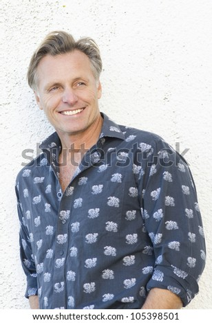 A color portrait of a pensive looking  handsome man in his forties leaning against a white wall. - stock photo