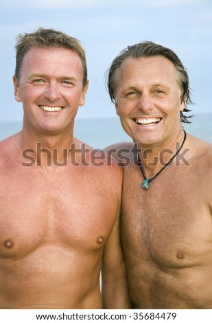 A color portrait of two happy mature gay men standing on the beach together. - stock photo