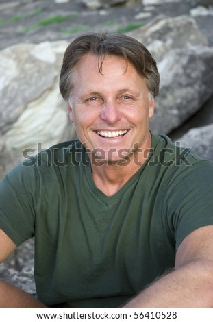 A color portrait photo of a handsome smiling man in his forties looking towards the camera. - stock photo