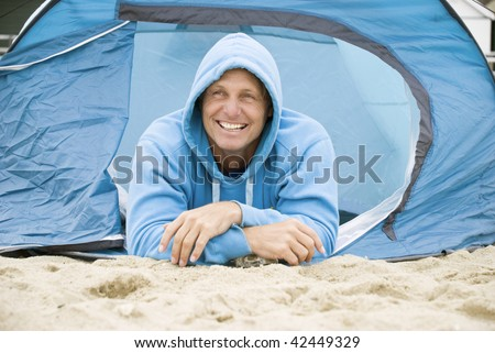A color portrait photo of a happy mature forties man camping on the beach. - stock photo