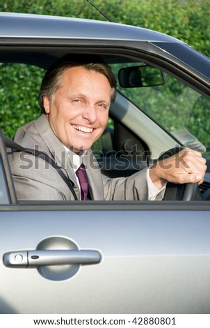 A color portrait photo of a happy smiling businessman sitting in his car. - stock photo