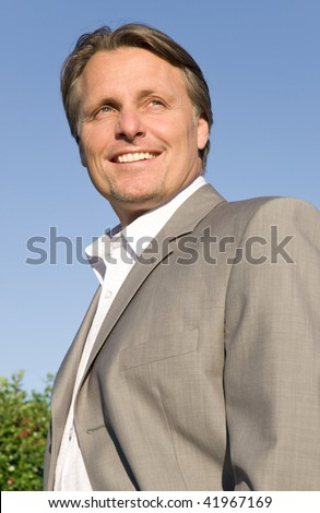 A color portrait photo of a happy smiling forties businessman standing outside - stock photo