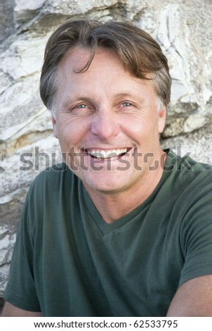 A color portrait photo of a happy smiling forties man looking straight at camera.