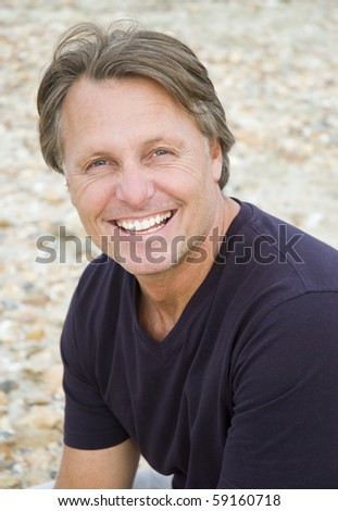 A color portrait photo of a happy smiling man in his forties looking straight at camera. - stock photo