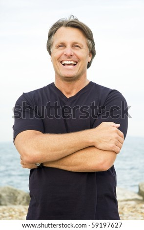 A color portrait photo of a happy smiling man in his forties standing on the beach - stock photo