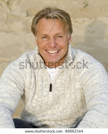 A color portrait photo of a happy smiling mature man in his forties sitting on the beach.