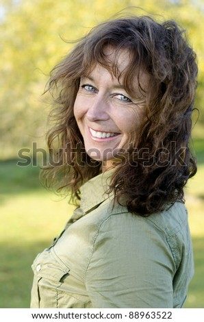 A color portrait photo of a happy smiling woman in her forties looking at camera. - stock photo