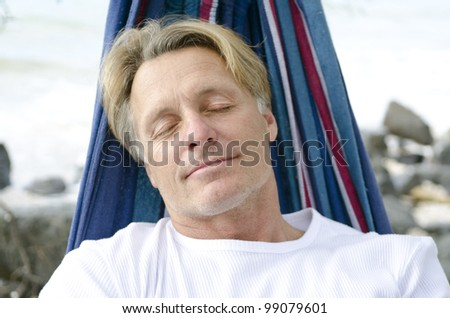 A color portrait photo of a mature man sleeping peacefully in a hammock on the beach. - stock photo
