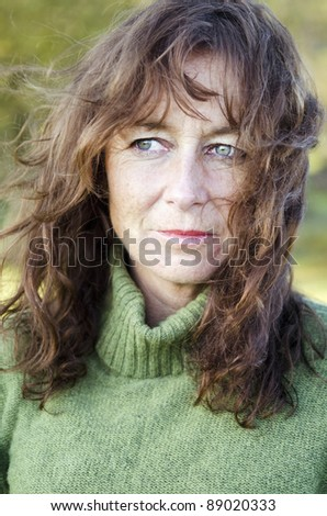A color portrait photo of a pensive and depressed looking mature woman in her forties.