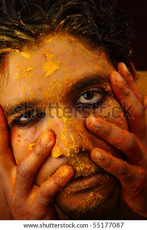A colored face with fingers on it - stock photo