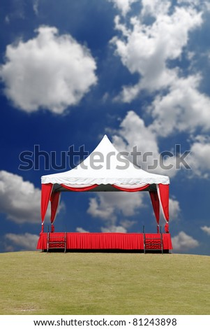 A colorful and cheerful outdoor performance stage with a tent, on a green grassy field against a blue cloudy summer sky. - stock photo